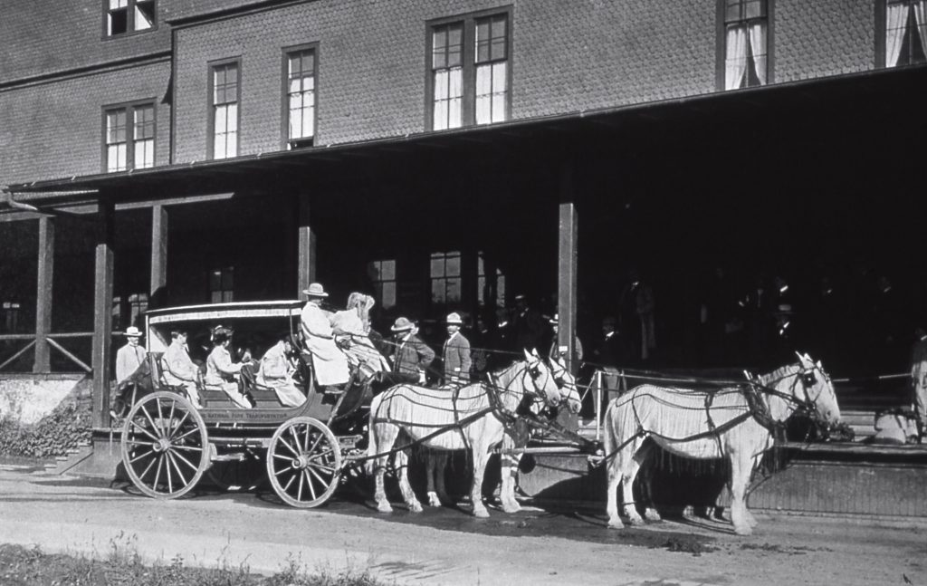 Stagecoach with passengers in front of a building