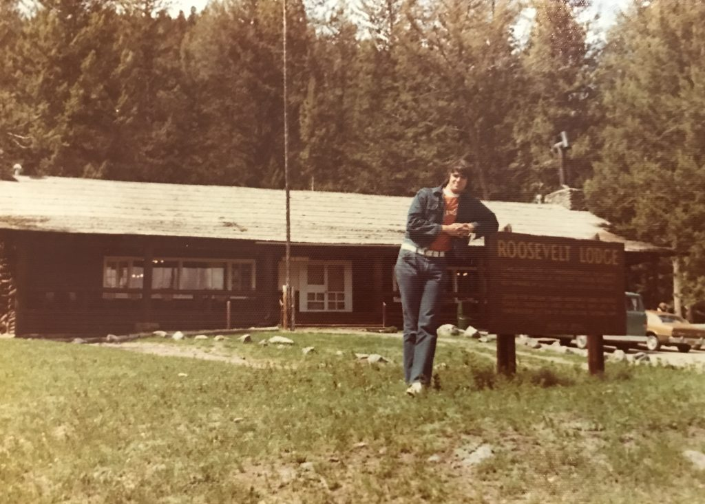 Jim leaning on Roosevelt Lodge sign