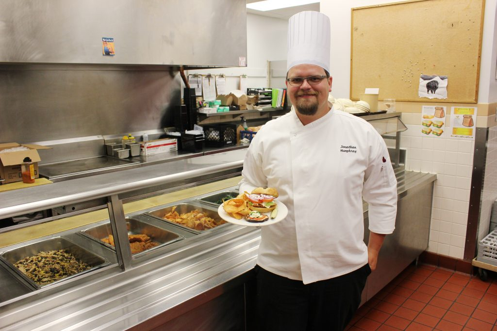 Chef JP Humphrey, holding a plated meal