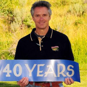 Jim holding a 40 years banner