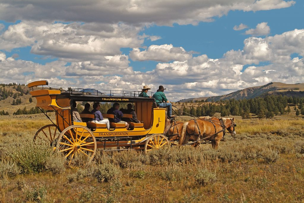 New stagecoach with passengers in a field