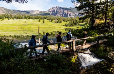Hikers crossing bridge in front of Trout lake
