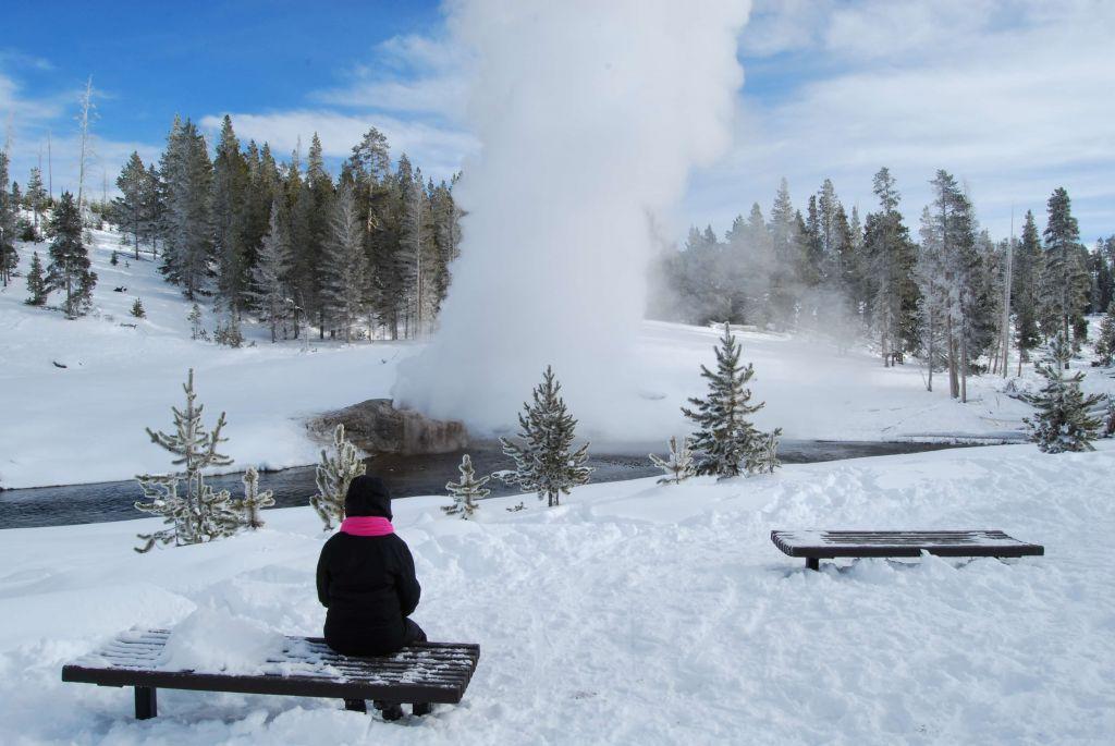 Woman sitting on bench watching Riverside Geyser erupt in winter