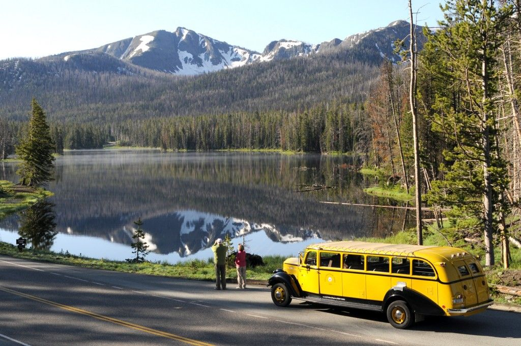 Historic yellow bus in front of a lake