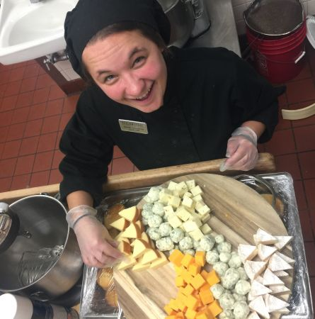 A Chef at Yellowstone preparing a plate of cheeses