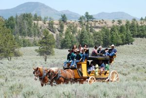 Passengers riding a stagecoach through a field with mountains in the background