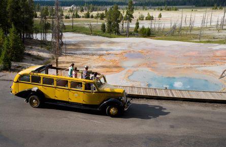 Yellow bus driving past firehole lake