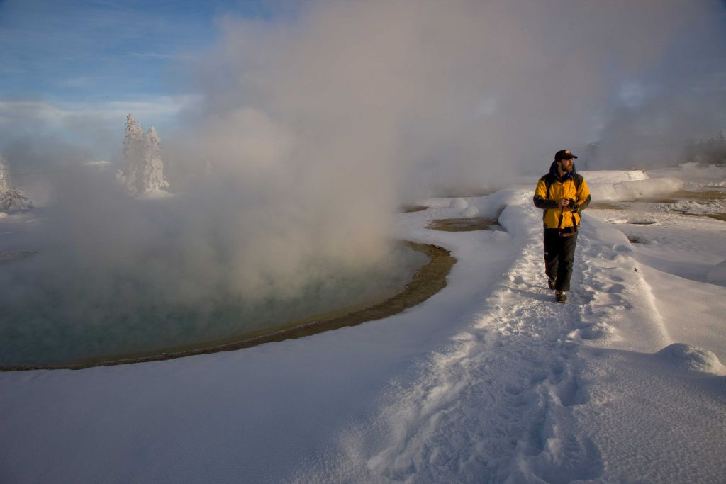 Tourist walking past a geyser in winter