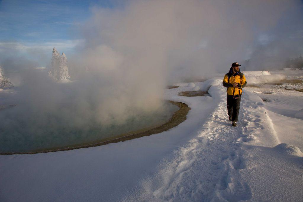 Tourist walking past a geyser in winter