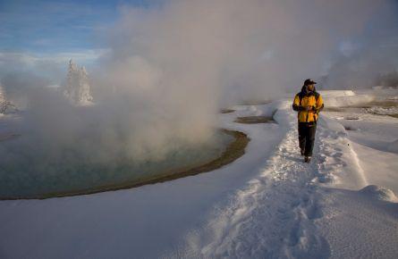 Tourist walking past a geyser