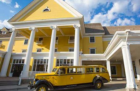Yellow bus in front of Lake Yellowstone Hotel