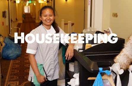 A smiling woman in a maid uniform next to a cleaning cart.