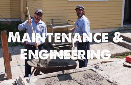 Smiling maintenance men shovel cement from a wheelbarrow.
