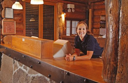 A smiling woman leaning on a reception desk.