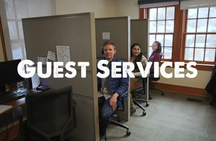Three smiling employees peeking out from their cubicles.