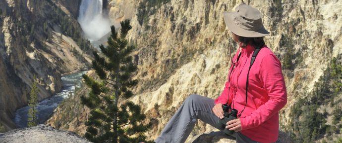 Woman with binoculars looking at waterfall