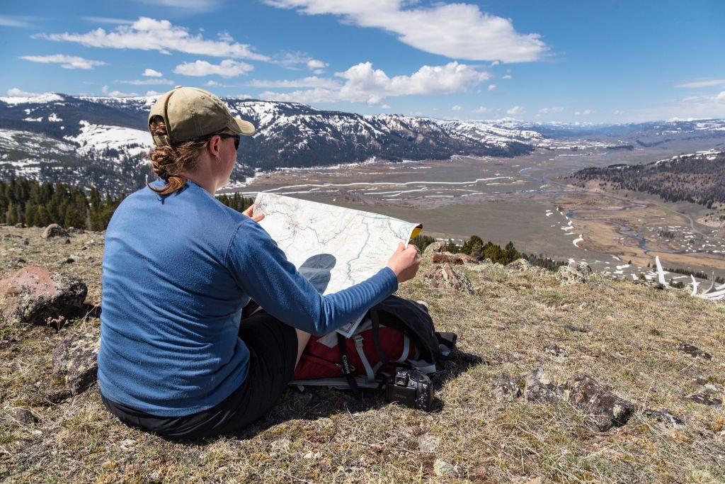 Hiker overlooking the Soda Butte Creek and Lamar River confluence with map