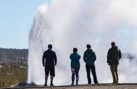 A group of tourists watching a geyser.